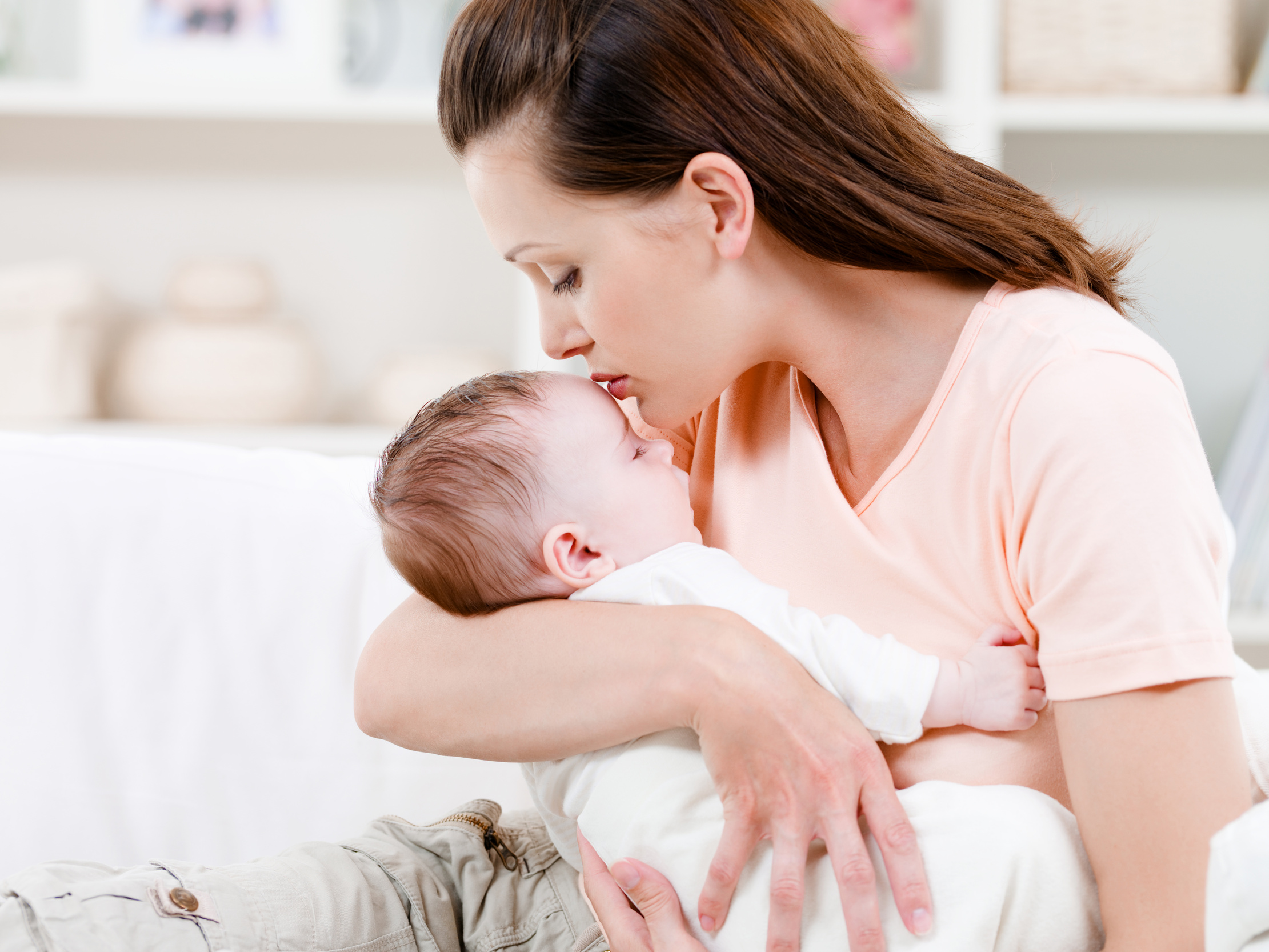 Young mother kissng her small sleeping newborn baby - indoors